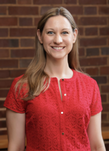 Headshot of Melanie Forehand. Subject is wearing a red dress and is standing in front of a brick wall.