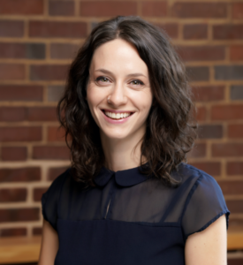 Headshot of Jennifer Gutman. Subject is wearing professional dress and standing in front of a brick wall.