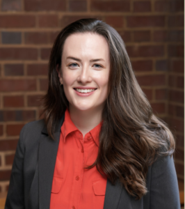 Headshot of Jessica Lowe. Subject is wearing professional dress and standing before a brick wall.