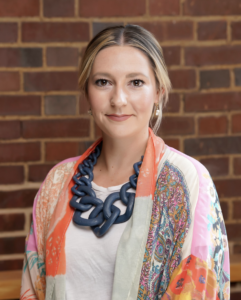 Headshot of Emma Reiners. Subject is wearing a multi-color shawl and professional dress.