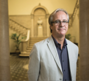 Image of Kevin Murphy. Subject is wearing professional dress and is standing between two pillars.