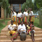 Photograph of seven African women wearing traditional dress and posing outside a brick building while holding instruments. Picture taken in Uganda.