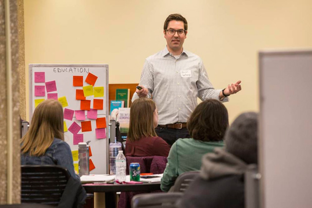 Kevin Galloway stands next to a board covered in yellow, pink and orange sticky notes. He has a presentation remote in one hand as he lectures to students seated at tables and chairs.