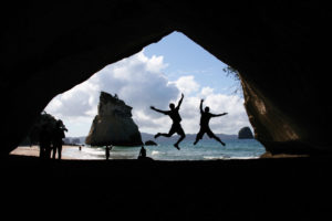 Students jumping in cave tunnel while abroad