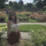 Nicole Gillis standing among many colorful flowerbeds outside on a sunny day