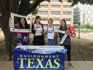 Four young women tabling outside with signs and flyers