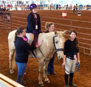 A girl sits happily on a horse. Alyssa Levitt, smiling, leads the horse by the reigns in a rodeo arena. Two women stand on either side of the horse.