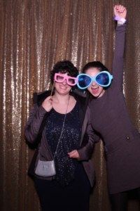 Alyssa Levitt poses for a photo with another student, wearing large, colorful glasses. In the photo, Alyssa punches her hand in the air in excitement.