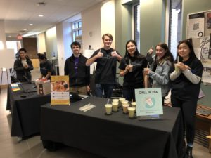 Photo of students standing behind an information table giving thumbs up with bubble tea
