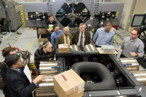 Eight men and one woman in professional attire wearing safety glasses and touring a factory space