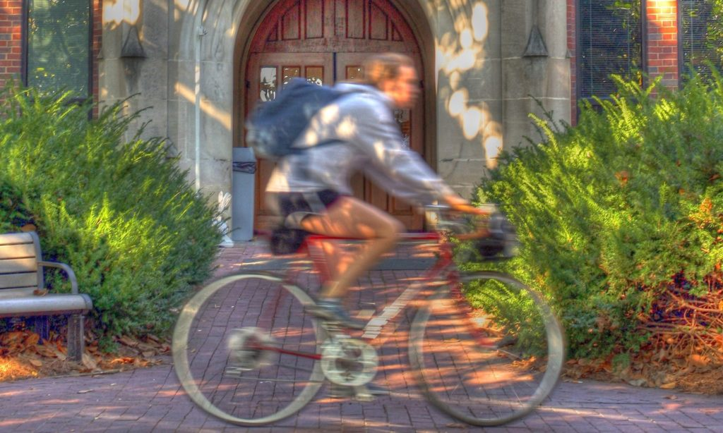 Person riding a bike past a building on campus