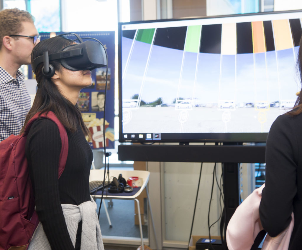 Person testing out Virtual Reality goggles at transportation research display at the FutureVU Mobility Expo.