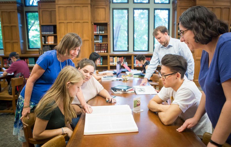 librarians assist students with projects at table in library study area