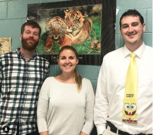 Biological Sciences lecturers Thomas Clements, Jessica Gilpin, and James Pask standing in front of a poster of tigers
