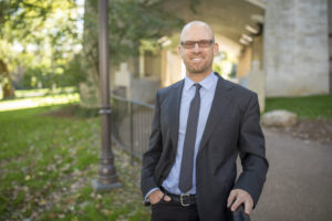 Portrait of Dr. Jonathan Metzl standing in front of a fence and building on Vanderbilt campus