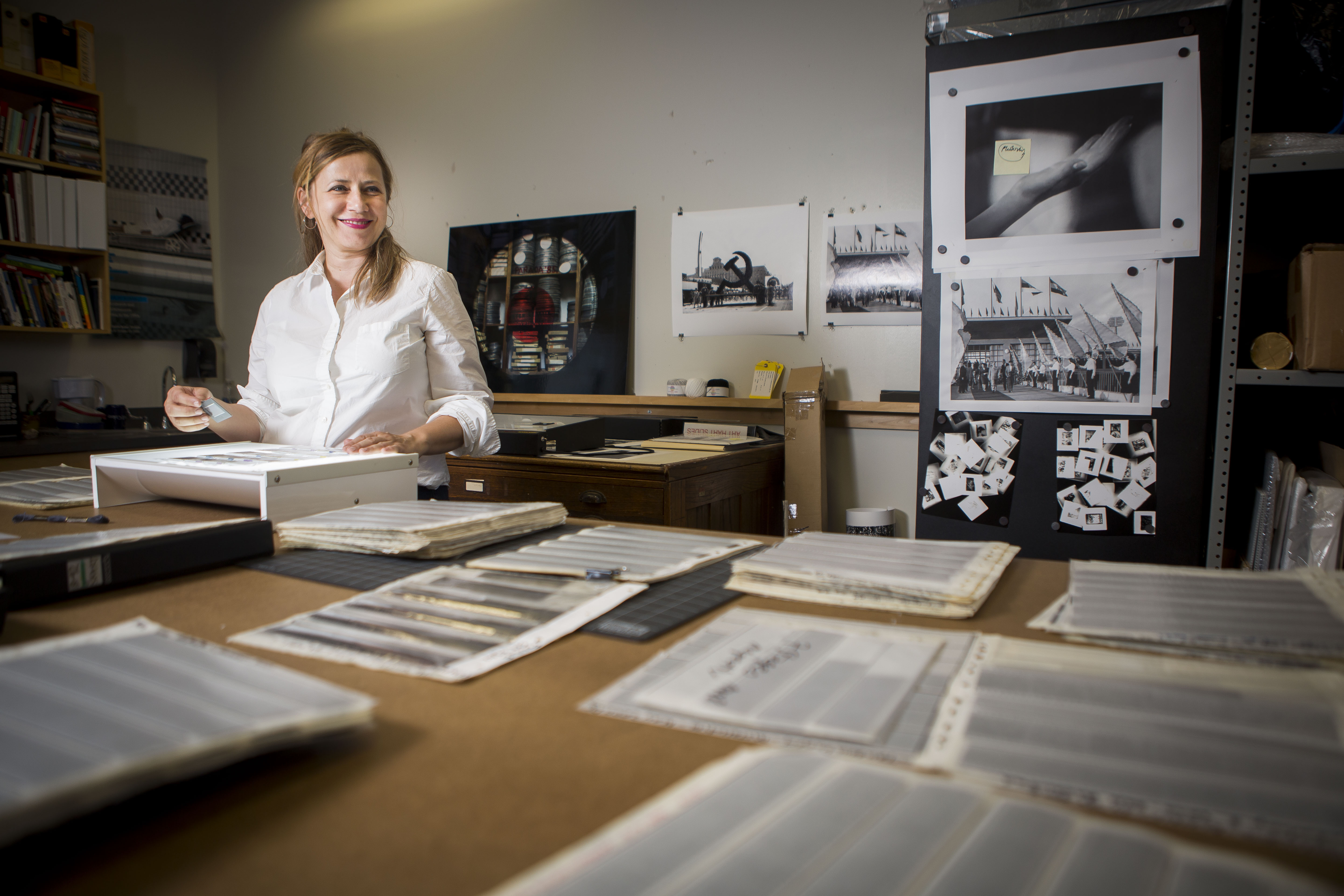 Vesna Pavlović standing at table surrounded by photos and documents