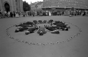 Black-and-white photo of women lying in a circle on the ground, surrounded by a ring of flowers