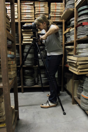 Vesna Pavlović taking photos with a camera and tripod, standing near shelves full of archived films