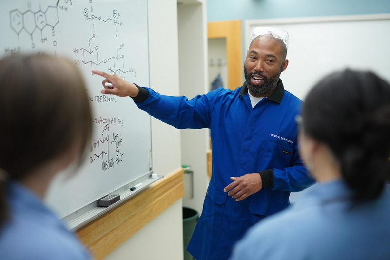 Two students watch and listen as Steve Townsend gestures to a white board containing diagrams of chemical structures