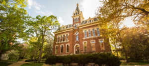 Front exterior of Benson Hall framed by leafy trees