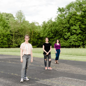 Photo of Jana Harper, Rebecca Steinberg, and Moksha Sommer standing in a parking lot with grass and trees in background