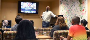 Rosevelt Noble giving a presentation to students in a commons room