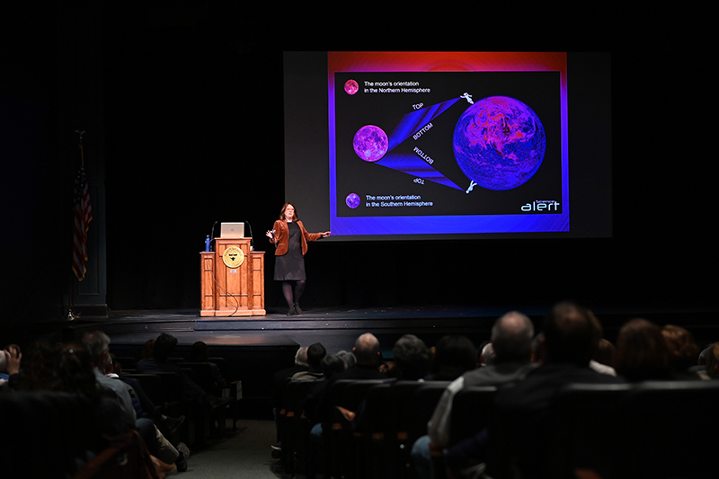 Susan Gessner Stewart stands on an auditorium stage in front of a projection screen showing diagrams of the moon.
