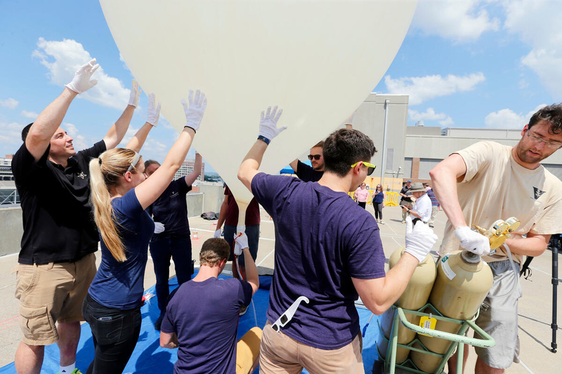 A student opens the valve on a gas tank as other students gather around an inflating weather balloon and place their hands on it to stabilize it