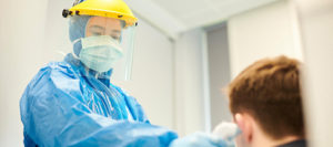a health care worker in full protective equipment takes the temperature of a patient who may have COVID-19