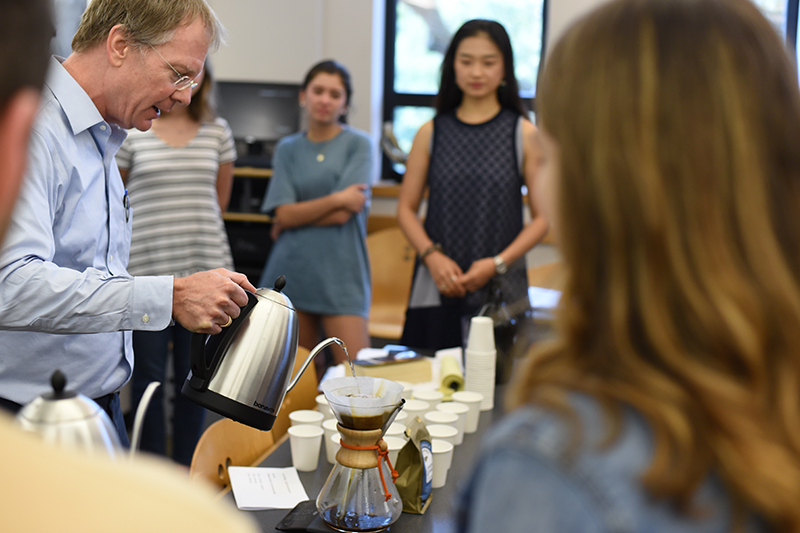 Ted Fischer pours water into a pourover coffee brewer as students watch