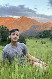Joe Miller sitting in a grassy field with mountains and trees in background