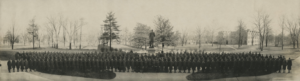 historic black-and-white photo of uniformed Vanderbilt World War One cadets standing in front of Cornelius Vanderbilt statue with trees in background
