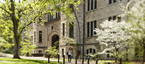 Exterior of Furman Hall, a gray stone building on the Vanderbilt campus, with blooming trees and a student walking by in the foreground