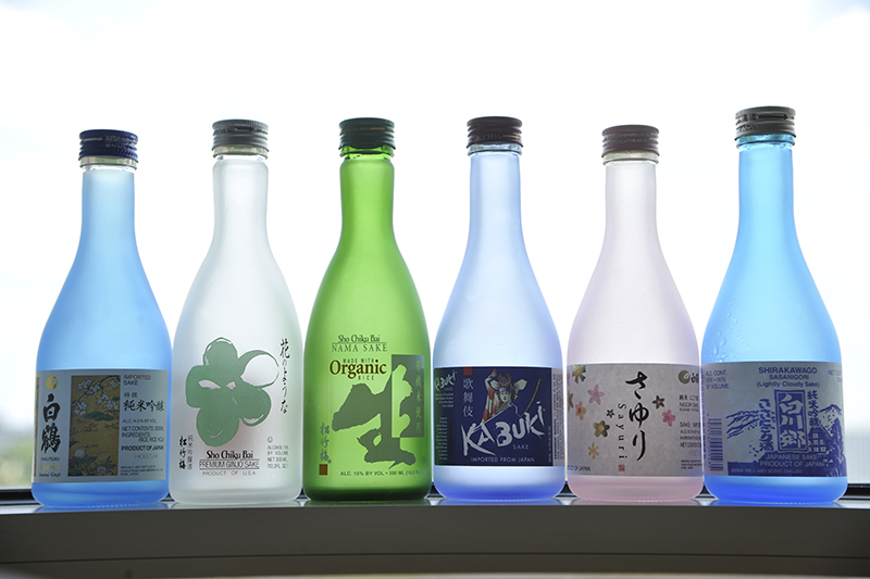 A row of blue, clear, and green translucent bottles bearing labels for various brands of saki, sitting on a windowsill in the Rokas Lab