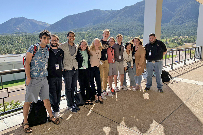 a row of students standing together on a paved terrace and smiling at the camera with tree-covered mountains in the background