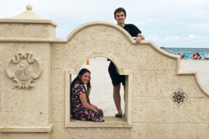 one student sits inside the archway of a stucco wall while another stands behind, with a beach and the ocean in the background