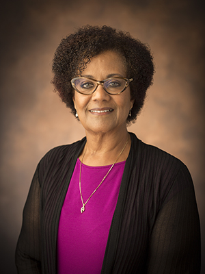 Associate Professor of African American and Diaspora Studies Tiffany Patterson wearing a pink blouse and black sweater and standing in front of a brown background