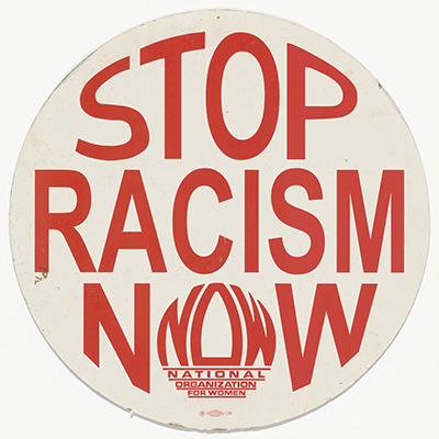 """circular cardboard placard with red text reading """"Stop Racism NOW,"""" with the """"O"""" in """"NOW"""" formed from the acronym of the National Organization for Women"""