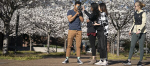 four students work on a film project outdoors on the Vanderbilt campus with white blooming dogwood trees in the background