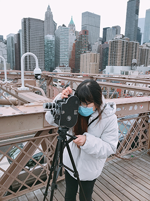 Linh Vu, wearing a tan coat and black leggings and a blue mask, looks through the viewfinder of a movie camera as she stands on a bridge with the New York City skyline in the background