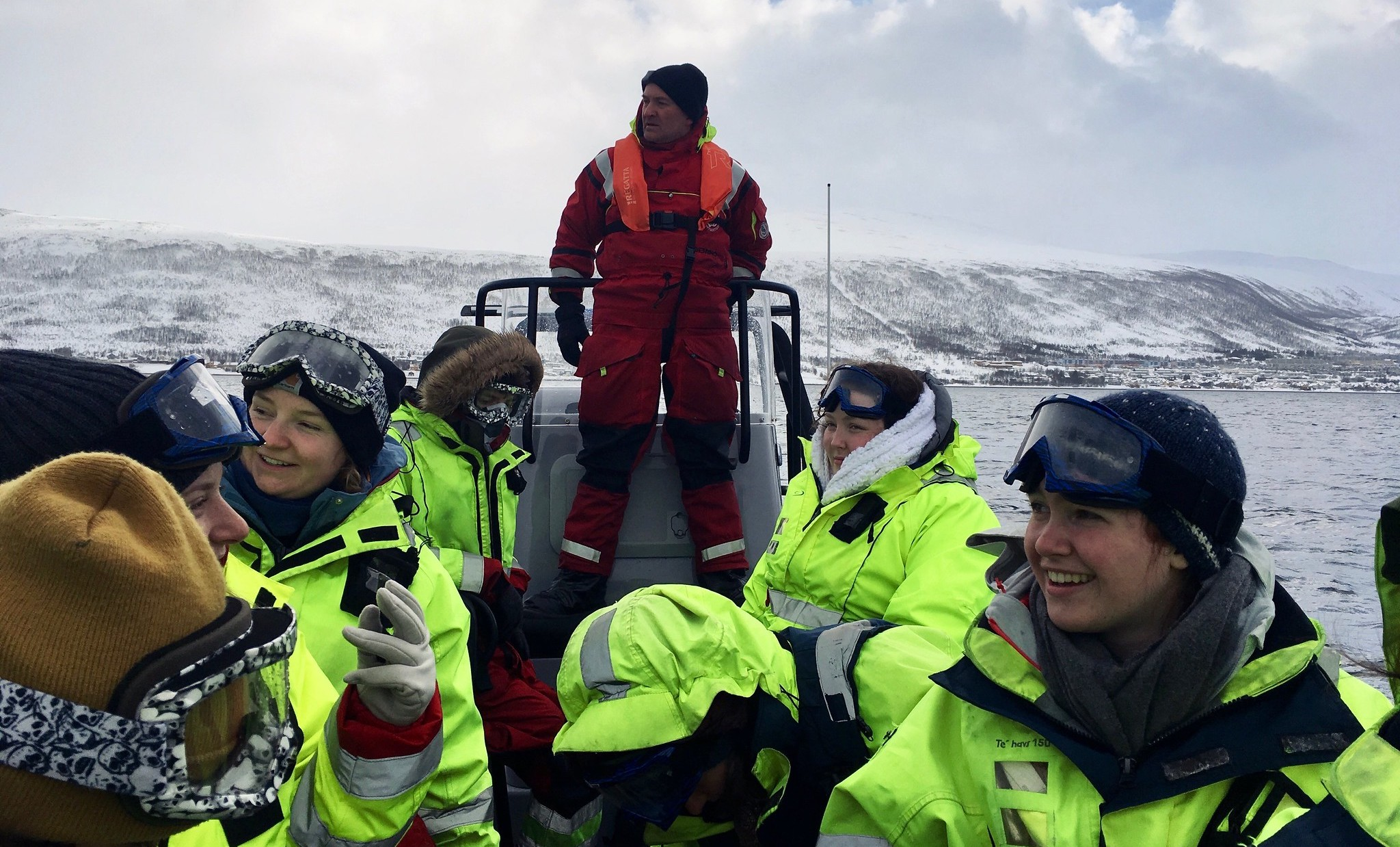 Students in a small research boat with snowy hills in background