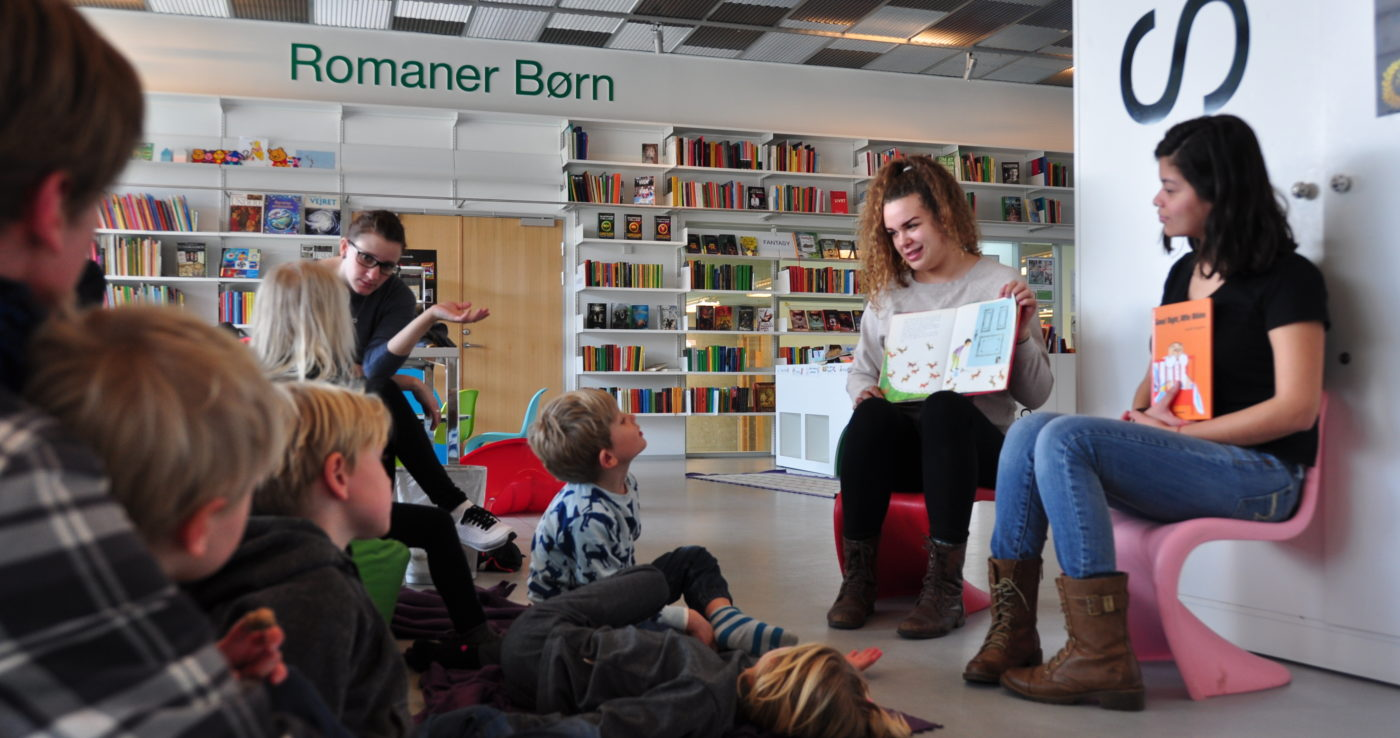 Preschool children being read to by college students in a library
