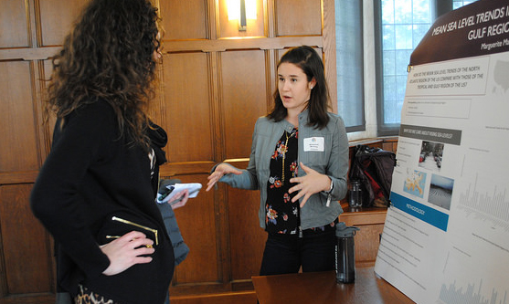 Photo of exhibit hall with participant discussing Marguerite Manning's presentation posters.