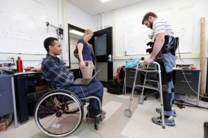 Ph.D. student Andrew Ekelem, seated, and physical therapist Christina Durrough work with exoskeleton test subject Dustin Fleeman. Photo by John Russell.