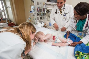 Amy Fleming, M.D., left, a close friend of the James family, checks on Eli during a hospital stay. Photo by Joe Howell.
