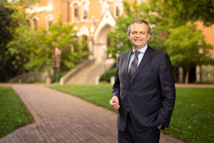 Chancellor Diermeier stands in a dark suit outside of Kirkland hall