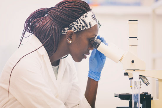 Photo of African American woman looking through a microscope